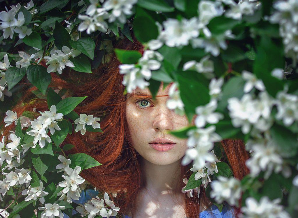 Жена маскирана зад цветя - снимка