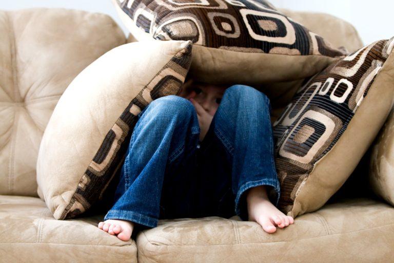 Страхливо момче покрито с възглавници - снимка